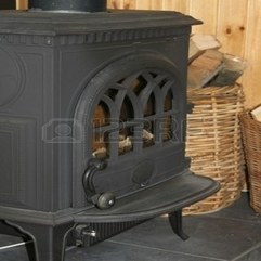 An Old Black Cast Iron Fireplace With Baskets Of Firewood Next - Karbonix