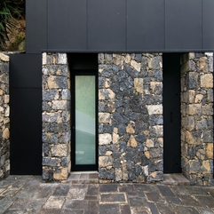 Door In Black Frame Placed Between Stone Wall Finishing Gazed - Karbonix