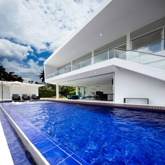 Interior Blue Infinity Pool With Wooden Floor Under Blue Sky - Karbonix